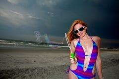 Mulher de cabelo consideravelmente vermelha dos jovens que joga em uma praia Imagens de Stock Royalty Free
