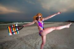 Mulher de cabelo consideravelmente vermelha dos jovens que joga em uma praia Fotografia de Stock