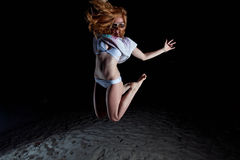 Mulher de cabelo consideravelmente vermelha dos jovens que joga em uma praia na noite Fotos de Stock Royalty Free