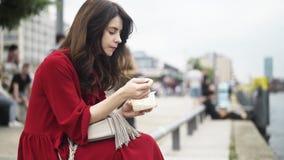 Mulher de cabelo escura bonita que come em uma rua alemão no verão video estoque