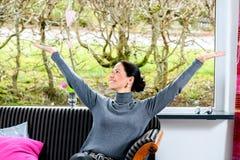 A mulher de cabelo escura está em casa feliz foto de stock royalty free