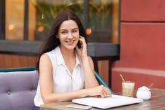 A mulher de cabelo escura positiva no equipamento branco, cercado com dispositivos modernos, senta-se na cafetaria, sorri delicad fotos de stock
