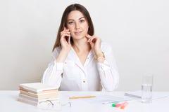 A mulher de cabelo escura de vista agradável tem a conversação através do telefone celular, envolvido no processo de trabalho, re foto de stock royalty free
