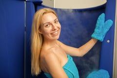 Mulher de cabelo loura que entra na cabine cryotherapy da sauna imagem de stock
