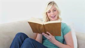 Mulher de cabelo loura que lê um livro video estoque
