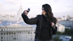 Mulher de cabelo preta nova que toma um selfie em um telhado filme