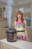 Mulher de cabelo vermelha com multicooker novo imagem de stock royalty free