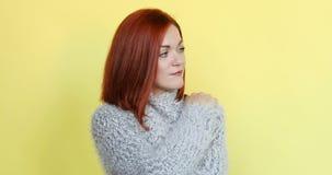 Mulher de cabelo vermelha na camiseta cinzenta que abraça-se que sonha aproximadamente morno na noite fria do inverno video estoque