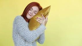 Mulher de cabelo vermelha de sorriso no descanso do abraço da camiseta, levantando no fundo amarelo filme