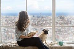 Mulher de cabelos compridos bonita com seu cão que aprecia a opinião da Espanha de Barcelona fora da janela foto de stock