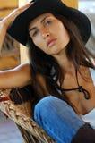 Mulher de cabelos compridos bonita do estilo country no chapéu negro e nas calças de brim que sentam-se em uma cadeira de vime imagem de stock royalty free