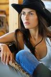 Mulher de cabelos compridos bonita do estilo country no chapéu negro e nas calças de brim que sentam-se em uma cadeira de vime fotografia de stock royalty free