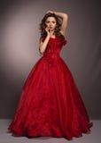 Mulher de cabelos compridos bonita no vestido vermelho imagem de stock