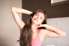Mulher de cabelos compridos nova feliz bonita que acorda imagem de stock