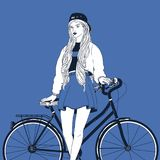 A mulher de cabelos compridos nova vestiu-se na roupa na moda que inclina a para trás na bicicleta da cidade Menina à moda com a  Imagem de Stock