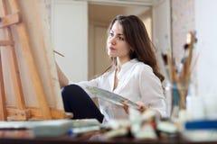 A mulher de cabelos compridos pinta a imagem na lona Imagens de Stock Royalty Free