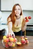 Mulher de cabelos compridos que toma pêssegos Fotos de Stock Royalty Free