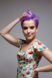 Mulher de cabelos curtos que guarda seu cabelo violeta com uma mão Fotografia de Stock Royalty Free