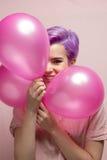 Mulher de cabelos curtos violeta na cor pastel cor-de-rosa que sorri atrás dos balões Imagem de Stock Royalty Free