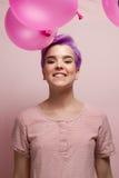Mulher de cabelos curtos violeta na cor pastel cor-de-rosa, sorrindo, com fal cor-de-rosa Fotos de Stock