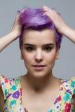 Mulher de cabelos curtos violeta que guarda seu cabelo com duas mãos Foto de Stock