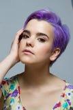 Mulher de cabelos curtos violeta que guarda sua cara Foto de Stock