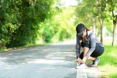 Mulher de corrida que amarra laços dos tênis de corrida antes de movimentar-se através da estrada no parque natural do exercício fotografia de stock royalty free