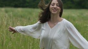 Mulher de dança exterior no vestido simples, rindo e sentindo próximo com natureza vídeos de arquivo