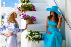 Mulher de dois viajantes que aprecia o branco, aleias pitorescas das ilhas de Cyclades em Grécia fotografia de stock royalty free
