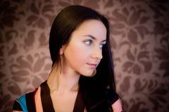 Mulher de encontro ao papel de parede com projeto floral Fotos de Stock Royalty Free