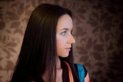 Mulher de encontro ao papel de parede com projeto floral Imagem de Stock Royalty Free