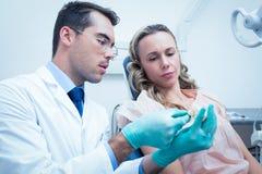 Mulher de ensino do dentista masculino como escovar os dentes imagem de stock