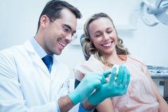 Mulher de ensino do dentista masculino como escovar os dentes foto de stock