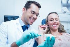 Mulher de ensino do dentista masculino como escovar os dentes imagens de stock