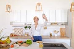 A mulher de fascínio guarda o telefone celular e chama a chamada video, estando Imagens de Stock