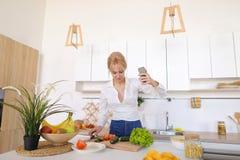 A mulher de fascínio guarda o telefone celular e chama a chamada video, estando Foto de Stock Royalty Free