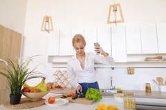 A mulher de fascínio guarda o telefone celular e chama a chamada video, estando Fotografia de Stock