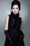 Mulher de fascínio no vestido e em luvas pretos Fotografia de Stock Royalty Free