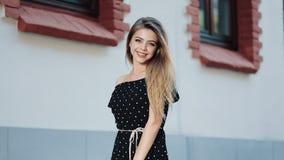 Mulher de fascínio nova no passeio de passeio do vestido preto 'sexy' através das ruas da cidade europeia velha Beleza natural vídeos de arquivo