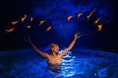 Mulher de Firedancer na água Fotografia de Stock Royalty Free