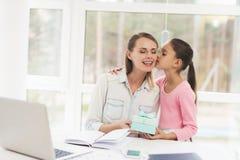 Mulher de funcionamento em licenças de parto A filha fez um presente para sua mãe amado Fotografia de Stock