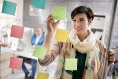 A mulher de funcionamento faz o esquema em etiquetas no local de trabalho Fotos de Stock