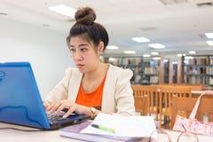 Mulher de funcionamento que datilografa um portátil do teclado Fotografia de Stock Royalty Free