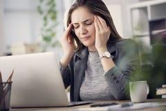 A mulher de funcionamento tem uma dor de cabeça fotografia de stock royalty free