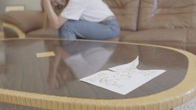 Mulher de grito irreconhecível no fundo do desenho das crianças rasgadas com a imagem da mamã e do paizinho que encontram-se no vídeos de arquivo