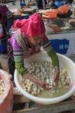 Mulher de Hani que vende o tofu no mercado local de Shengcun em YuanYang Hani é uma das 56 minorias em China e é nativo de Yua Foto de Stock