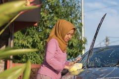 Mulher de Hijab que limpa seu carro fora Servi?o do auto do transporte, conceito do cuidado foto de stock royalty free