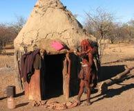 Mulher de Himba que está na frente da cabana Fotos de Stock