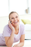 Mulher de incandescência que fala no telefone que encontra-se no assoalho fotografia de stock royalty free