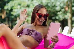 Mulher de irradiação que tem o bate-papo video ao nadar na associação imagem de stock royalty free